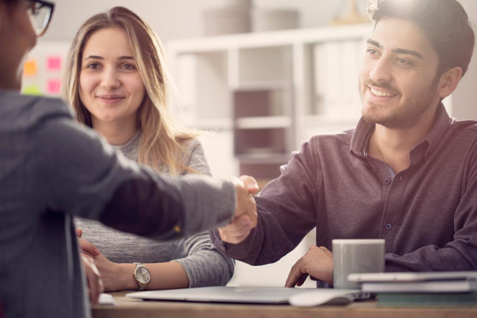 smiling young couple shaking hands with tax consultant